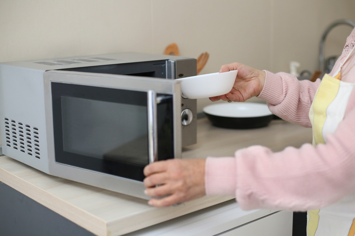 An elderly woman preparing cat food using a microwave oven