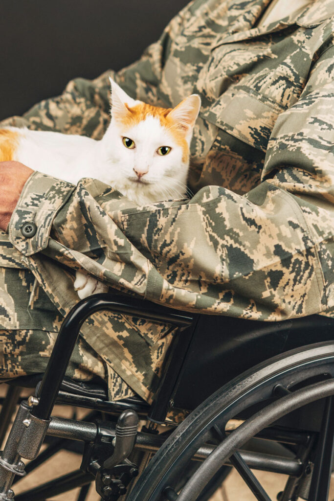 Disabled military service member holding his cat in a wheelchair to help with the feeling of anxiety or depression