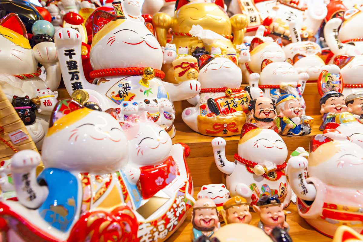 Group of Maneki Neko displayed in shop – lucky cat, common Japanese lucky charm, talisman which is often believed to bring good luck to the owner, What is the Maneki Neko Cat?
