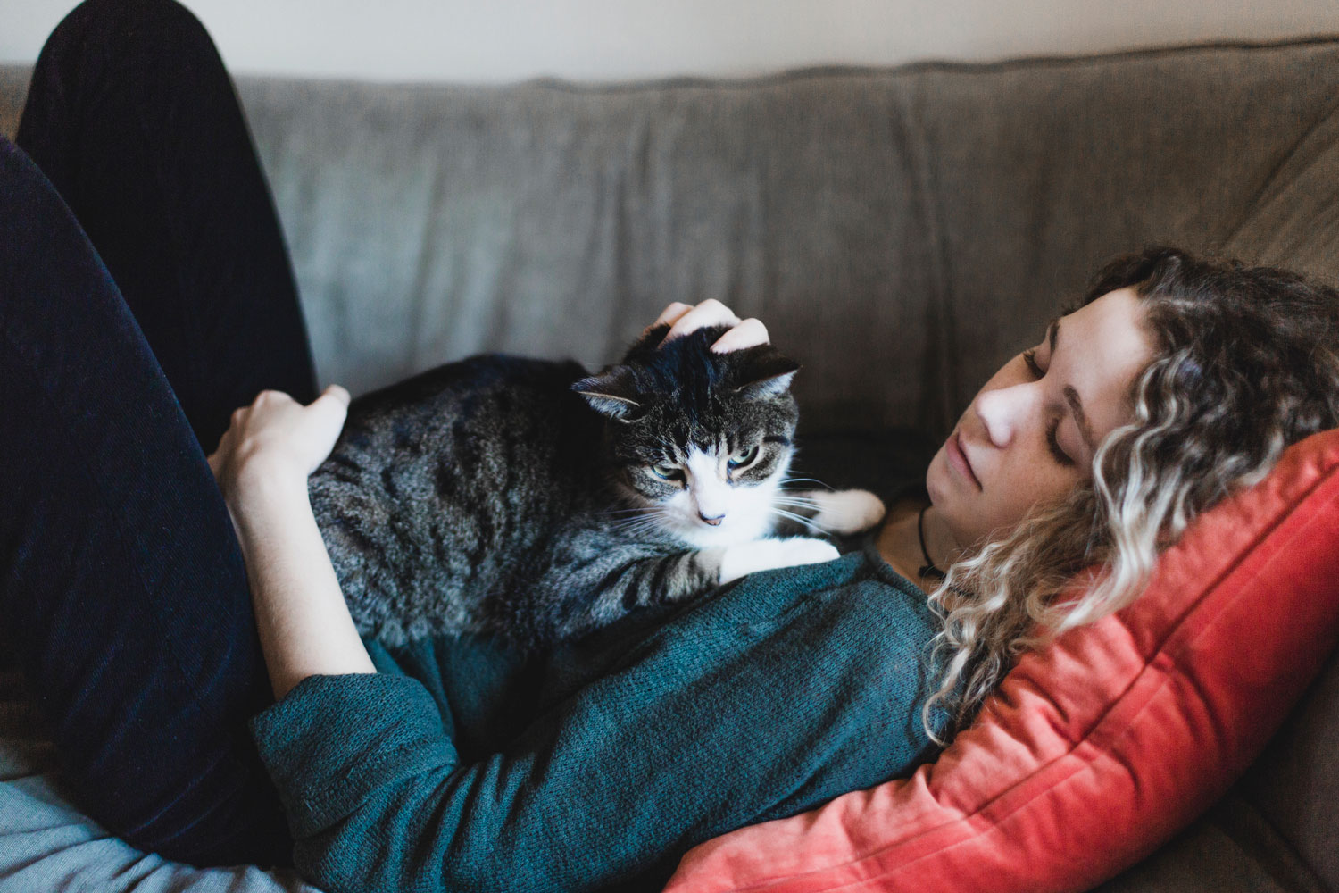 A woman lying on the couch while petting her cat that's lying on her chest