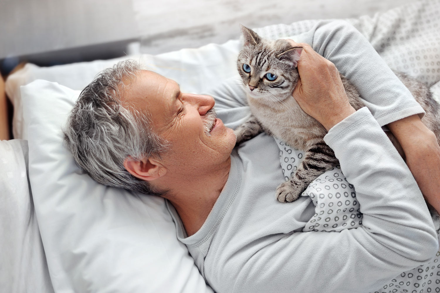 An elderly man lying on the bed while petting his cat
