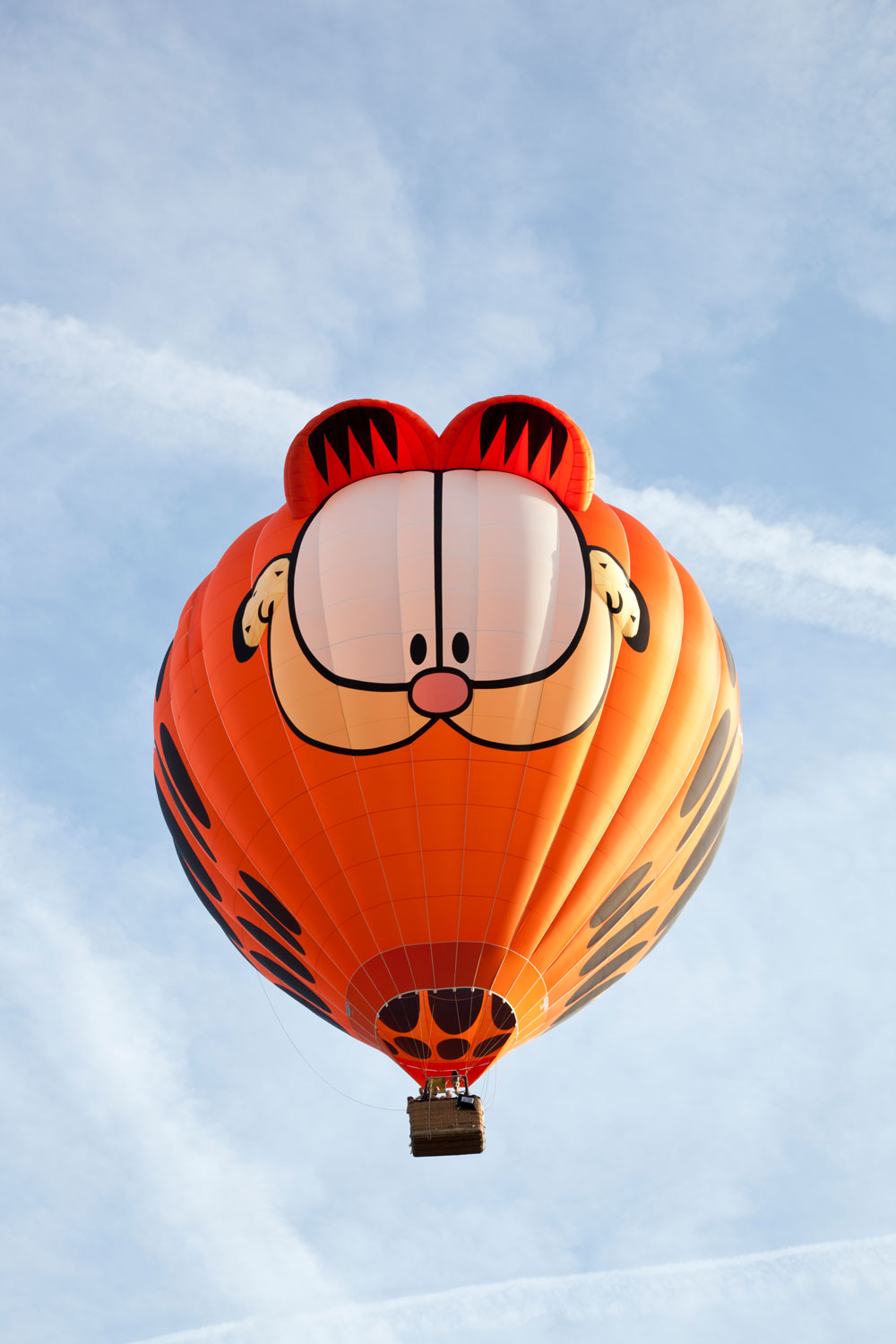 A huge Garfield themed air balloon flying in the sky